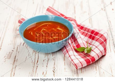 Tomato soup and basil on wooden table