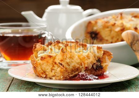 Panettone pudding and steaming hot black tea on shabby wooden background closeup