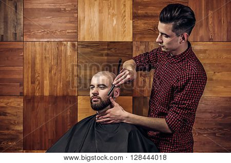Client during beard shaving in barbershop. Portrait of young bald bearded man getting shaved with straight edge razor by hairdresser at barbershop on a wooden texture.