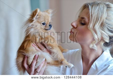Beauty bride in dressing gown with a cute dog indoors. Beautiful model girl in colorful wedding robe with puppy. Female portrait of cute lady. Woman with hairstyle