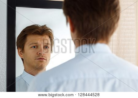 Portrait of sad young businessman with unhappy face looking at the mirror. Man preparing for important meeting, new job interview or dating. Difficult relationship, stress management concept