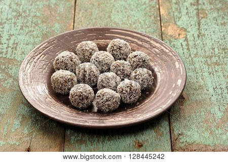 Homemade raw vegan sweets in coconut shavings in ceramic plate on old wooden table closeup