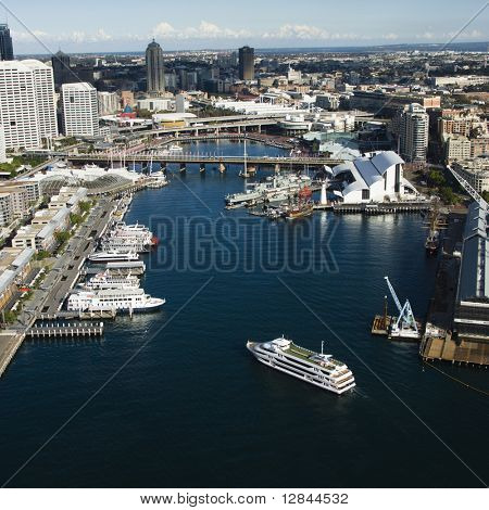 Aerial view of ships and boats in Darling Harbour with view of skyscrapers in Sydney, Australia.