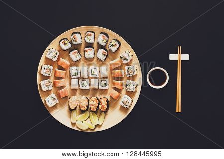 Japanese food restaurant, sushi maki gunkan roll plate or platter set. Chopsticks, ginger and wasabi. Sushi at bamboo round plate, black background. Top view with soy sauce and lime