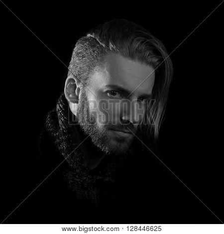Close-up of young man portrait black and white. Young serious business man with serious eyes against black background