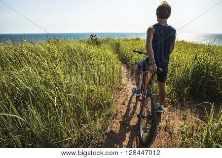Young rider with bicycle standing in a green lush meadow