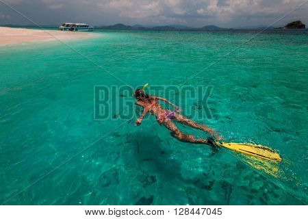 Lady with snorkel and fins swims near the shore