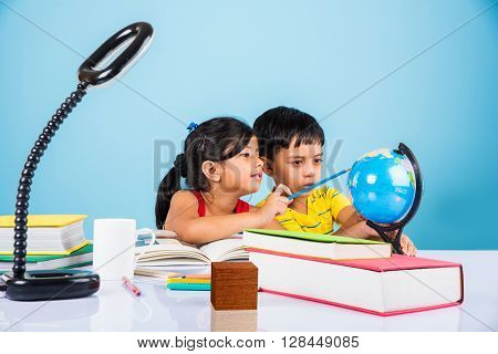 indian boy and girl studying with globe on study table, asian kids studying, indian kids studying geography, kids doing homework or home work, two kids studying on table