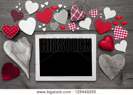 Chalkboard With Copy Space For Advertisement. Many Red Textile Hearts. Wooden Background With Vintage, Rustic Or Retro Style. Black And White Image With Colored Hot Spots.