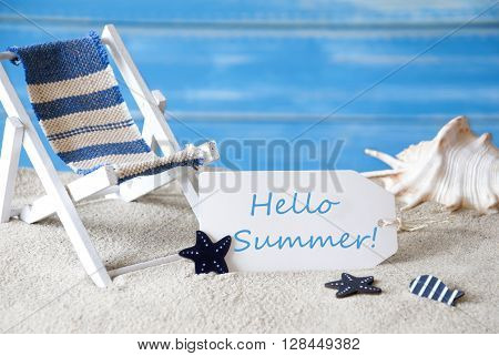 Summer Label With English Text Hello Summer. Blue Wooden Background. Card With Holiday Greetings. Beach Vacation Symbolized By Sand, Deck Chair And Shell.