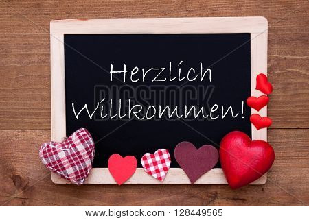 Blackboard With German Text Herzlich Willkommen Means Welcome. Red Textile Hearts. Wooden Background With Vintage, Rustic Or Retro Style.
