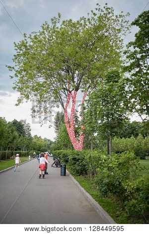 MOSCOW, RUSSIA - JUN 29, 2015: People have rest in recreation Gorky Park. The installation Ascension of Polkadots on the Trees wrapped in fabric covered with Yayoi Kusama signature polka dot motif.