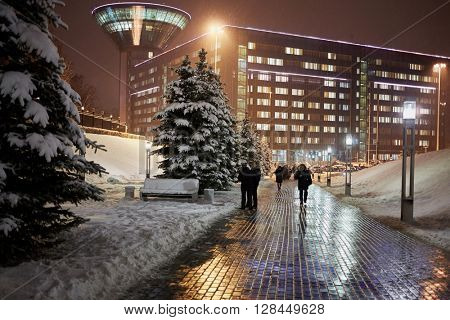 RUSSIA, KRASNOGORSK - DEC 12, 2014: People walk in winter evening near complex of the House of Moscow Oblast Government. Construction of House was started in 2004 and ended in 2007.