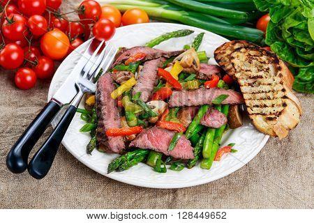 Grilled steak with stir-fried vegetables on plate