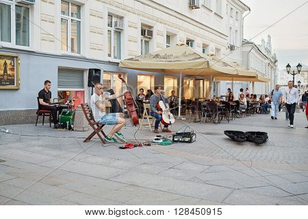 RUSSIA, MOSCOW - JUN 22, 2015: People walk along Kuznetsky Most street near outdoor cafe with live music.