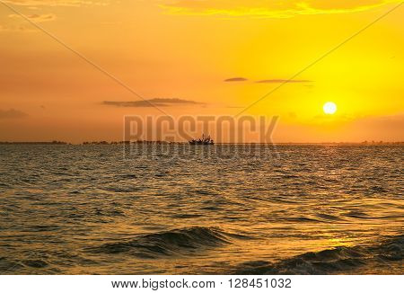 FORT MYERS BEACH, USA - MAY 12, 2015: Silhouette of a fishing boat on the Gulf of Mexico backed by an orange sunset sky.