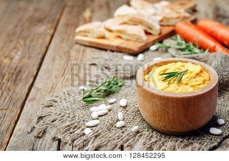 roasted carrots rosemary white bean hummus on wooden background