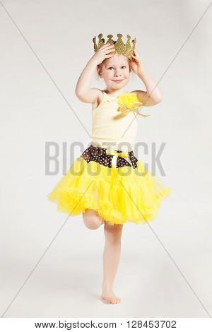 Little girl in yellow with crown on her head