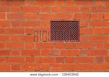 Closeup background texture photo of red brick wall with air vent, ventilation