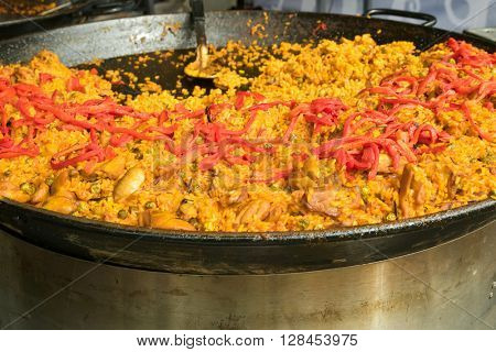 Soft focus of Valencian rice dish, Chicken paella garnished with seared red bell pepper strips cooked in a large shallow pan