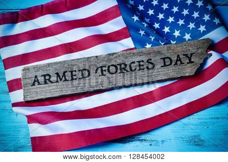 the text armed forces day written in a piece of wood and a flag of the United States, on a blue rustic wooden background, with a slight vignette added