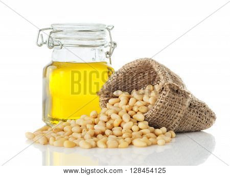 cedar oil in a glass jar and peeled pine nuts closeup isolated on white background