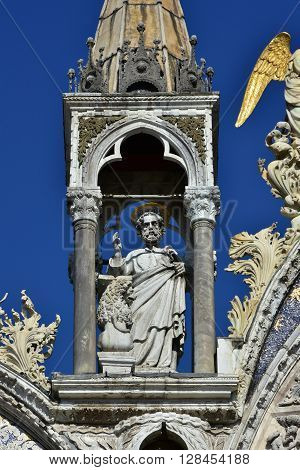 Medieval statue of Mark the Apostle with small lion from Saint Mark basilica monumental facade in Venice