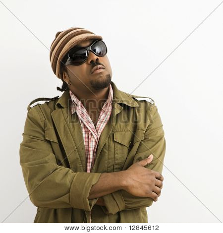 African-American mid-adult man wearing hat and sunglasses with arms crossed looking up.