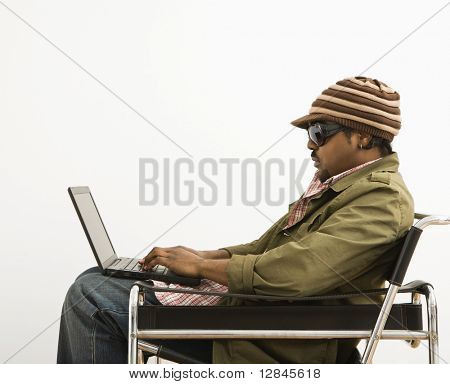 Side view of African-American mid-adult man wearing hat and typing on laptop computer.