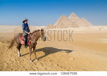 Tourist on horseback in front of the Great pyramid of Giza complex, Egypt.