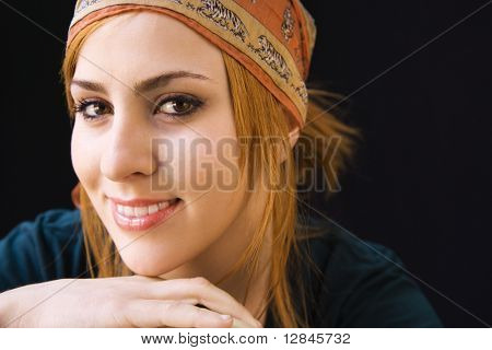 Young redheaded woman wearing cap smiling at viewer.