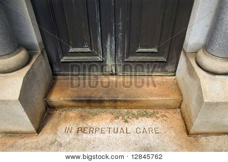 "Entrance to mausoleum in graveyard with words, ""In Perpetual Care"""