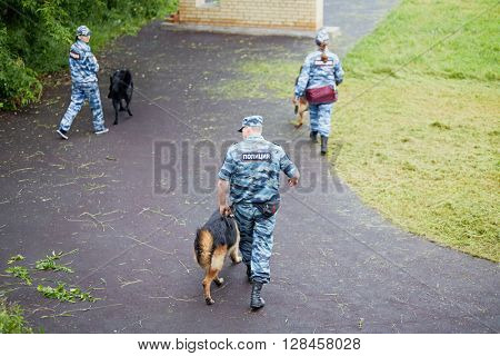 MOSCOW, RUSSIA - JUN 26, 2015: Group of policemen with dogs cross the courtyard of police department.