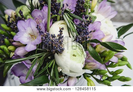 Beautiful spring bouquet of wedding flowers buttercup ranunculus, freesia, lavender nature background. Pastel colors purple, green. Still life concept. Rustic style. Holiday wedding floristic, bouquet of bride. Modern marriage.