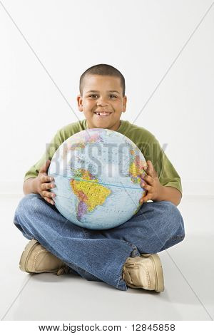 Young latino adolescent boy sitting with globe.