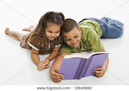 Hispanic brother and sister reading book together.