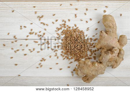 Spreaded pearl barley and ginger on wooden panel. Natural remedy. Weight loss. Helping prevent gallstones. Improves skin elasticity. Improving heart disease risk factors. Treating chronic indigestion. Reducing cholesterol levels. Reducing muscle pain and