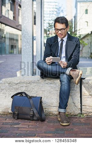 Young smiling asian business man looking at mobile phone sitting outside on city street