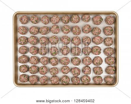 Cooking tray with rows of prepared homemade meatballs, overhead view isolated on white background