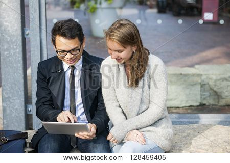 Two happy young people looking into digital tablet sitting outside on city street with copy space