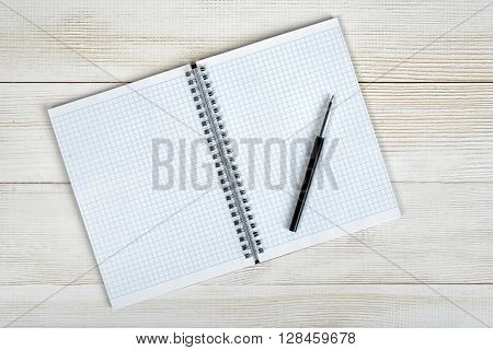 Top view of open empty notebook and black pen on it. Workplace of office man. Readiness for the new. Beginning of something new. Lack of knowledge. First work day. Office stuff.