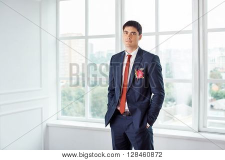 Gorgeous smiling groom looking at camera. Handsome man in a suite with a buttonhole standing against a window indoors