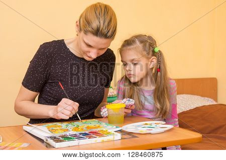 Girl Artist Teaches A Little Girl At The Table As A Draw Watercolor On Paper