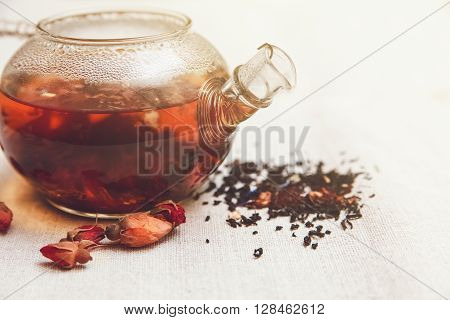 The Dry Red Small Roses with Black Tea in the Glass Teapot,Tea Drinking,Aromatized Flowers,Table Rough Linen Tableclose;Toned