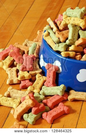 An over abundant supply of various dog treats flowing from a dish.