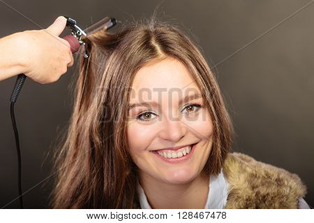 Stylist curling hair for pretty woman. Girl care about her hairstyle
