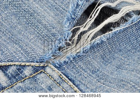 Torn blue jeans background close up DOF