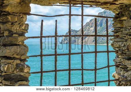 An old window with fantastic mountain sea view in Malcesine, Italy.