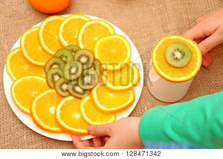 fruits of slices oranges and kiwis in a white plate exposed to nice illustrations alongside a cup of it as fruit orange and kiwi