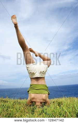 Young woman doing headstand in grass near ocean in Maui, Hawaii.